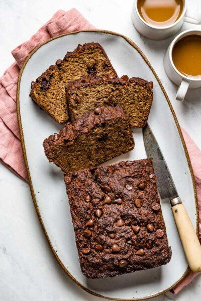 A few slices of Almond Flour Banana Bread served on a plate with two cups of coffee on the side photographed from the top view
