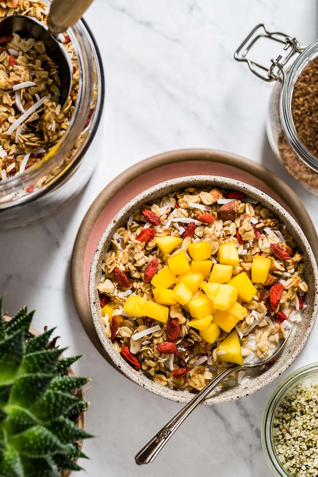 Easy and Healthy Granola Recipe (Vegan and Gluten Free) placed on a bed of granola and fruit as a topping and photographed from the top view.