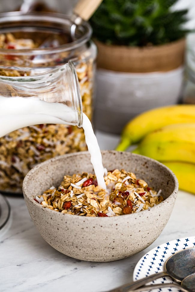 The Best Low Sugar Chunky Granola Recipe is placed in a bowl and photographed from the front view as it is being drizzled with milk