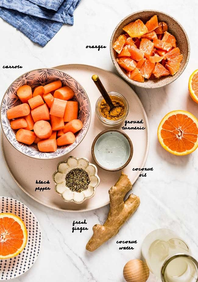 Ingredients for Orange Ginger Turmeric smoothie are photographed from the top view on a white marble backdrop.