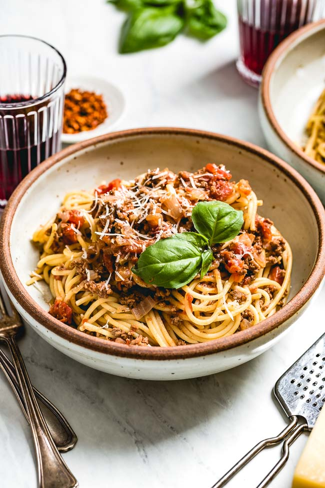 A bowl of Spaghetti Bolognese Sauce is placed in a bowl and photographed from the front view.