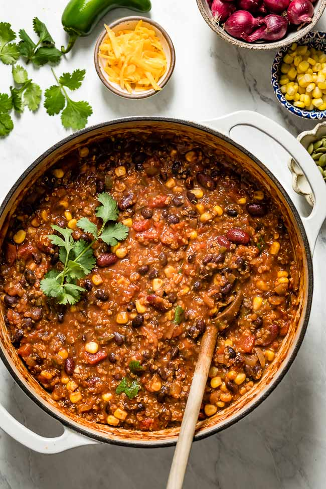 A big pot of vegetarian chili with quinoa photographed in a large pot from the top view