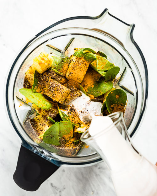 Turmeric Green Smoothie ingredients are placed in a blender and photographed from the top view as a woman is pouring almond milk into the blender