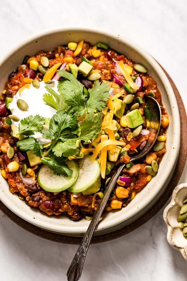 A bowl of Vegan Chili with Quinoa Recipe is photographed from the top view from a close up distance.