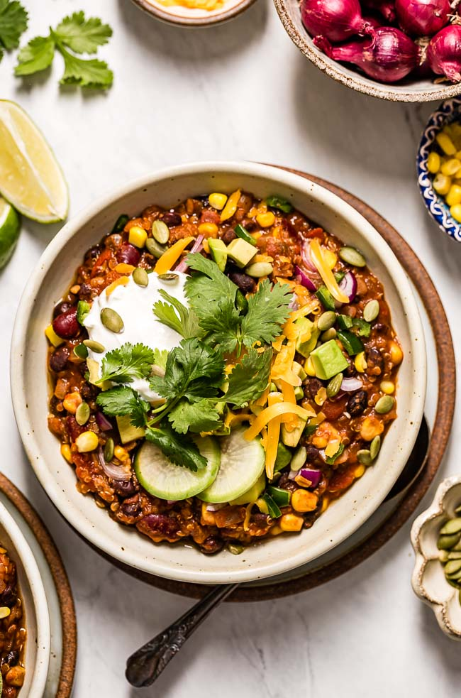A bowl of Vegetarian Quinoa Chili Recipe is topped off with cheese, avocados, and cilantro