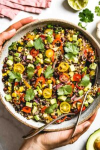 A big bowl of Southwestern Quinoa Salad is photographed from the top view as a woman is placing it on the table
