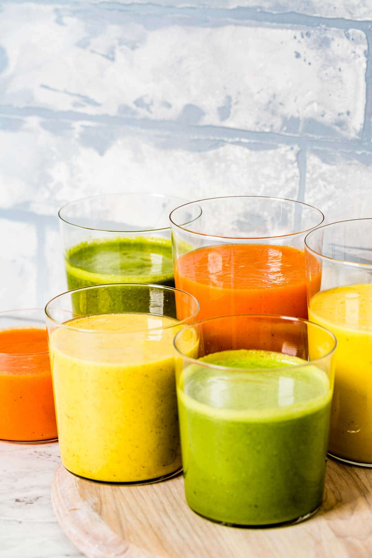 Three different kinds of turmeric smoothie recipes are placed in glasses and photographed from the front view.
