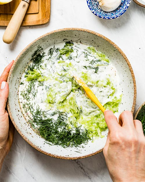 A woman is mixing Mediterranean yogurt sauce with dill