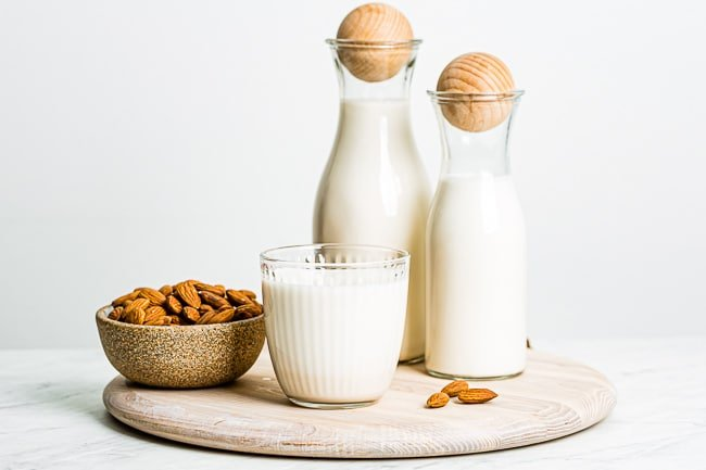 Raw Almond milk in a glass and in bottles