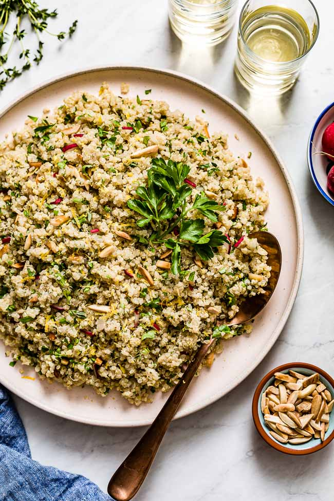 Herbed lemon quinoa served in a large plate with fresh parsley, sliced almonds, and lemon.