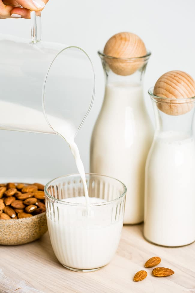 A woman is pouring a glass of almond milk