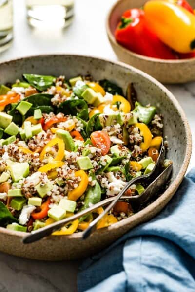 Quinoa Avocado Salad in a bowl with two spoons front view