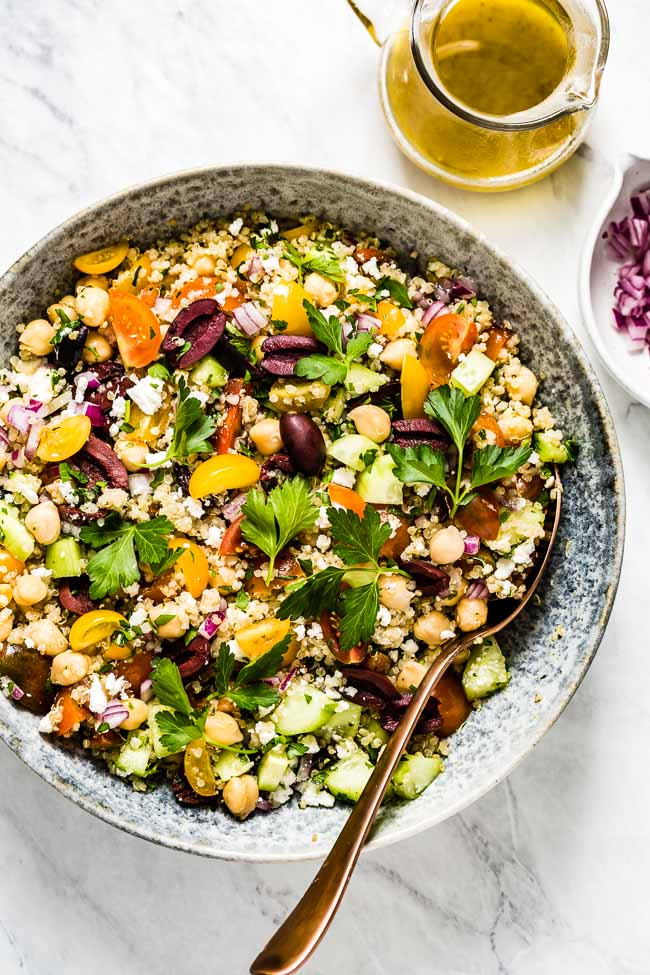 A bowl of Greek Quinoa Salad served wit lemon vinaigrette on the side