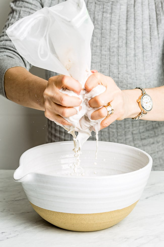 A woman is squeezing a nut milk bag to extract all the milk out of it