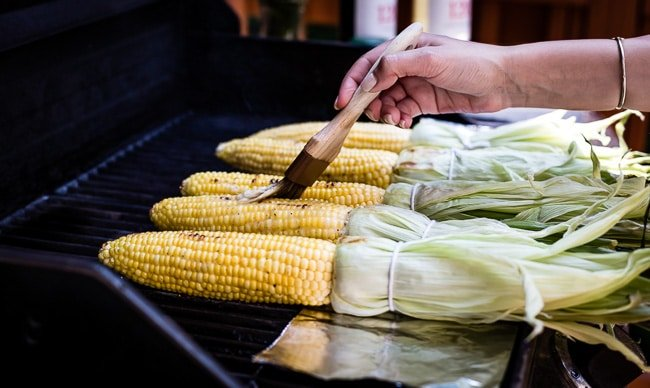 A woman is brushing corn on the cob with butter