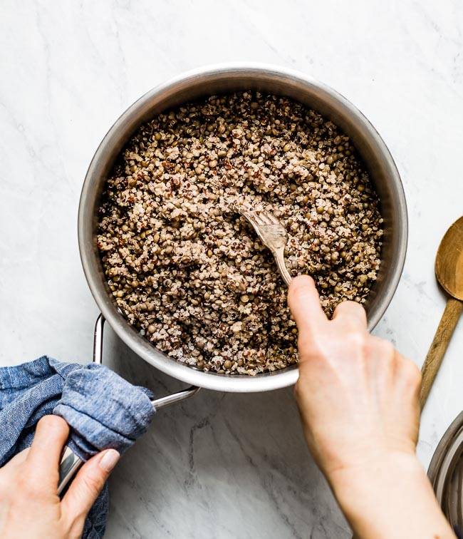 A woman is fluffing quinoa from after it is cooked