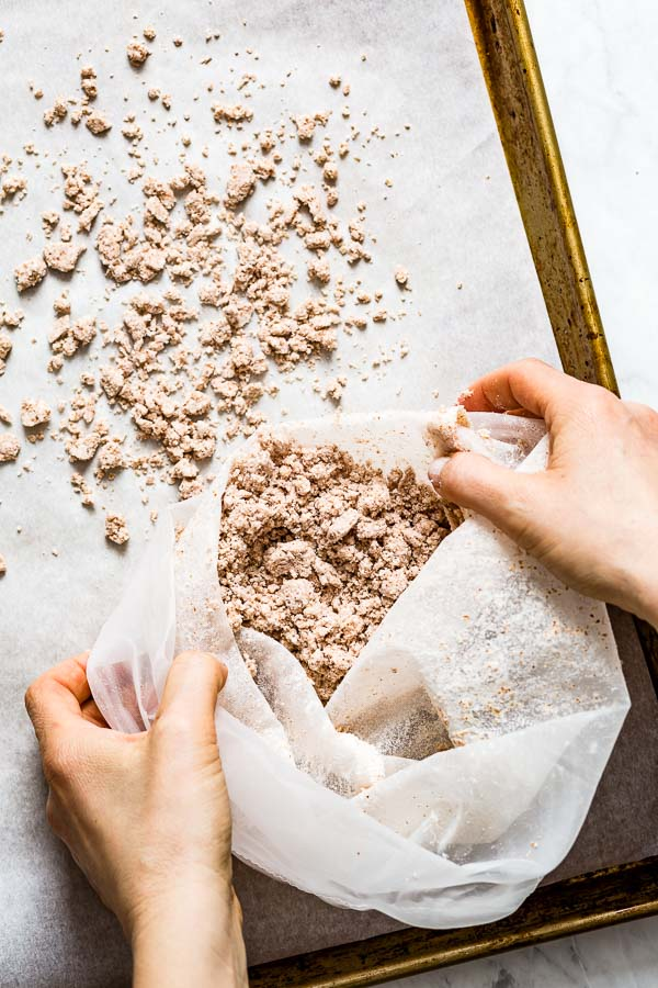 A woman is spreading almond pulp on a baking sheet