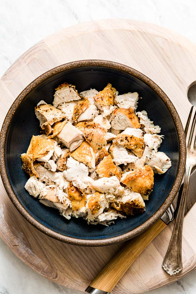 A bowl of sliced oven baked bone in chicken with a fork and knife on the side.