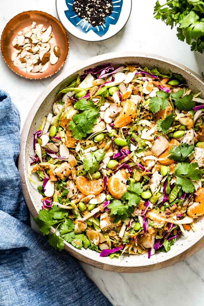 A big bowl of Asian Sesame Chicken Salad garnished with tangerines and cilantro