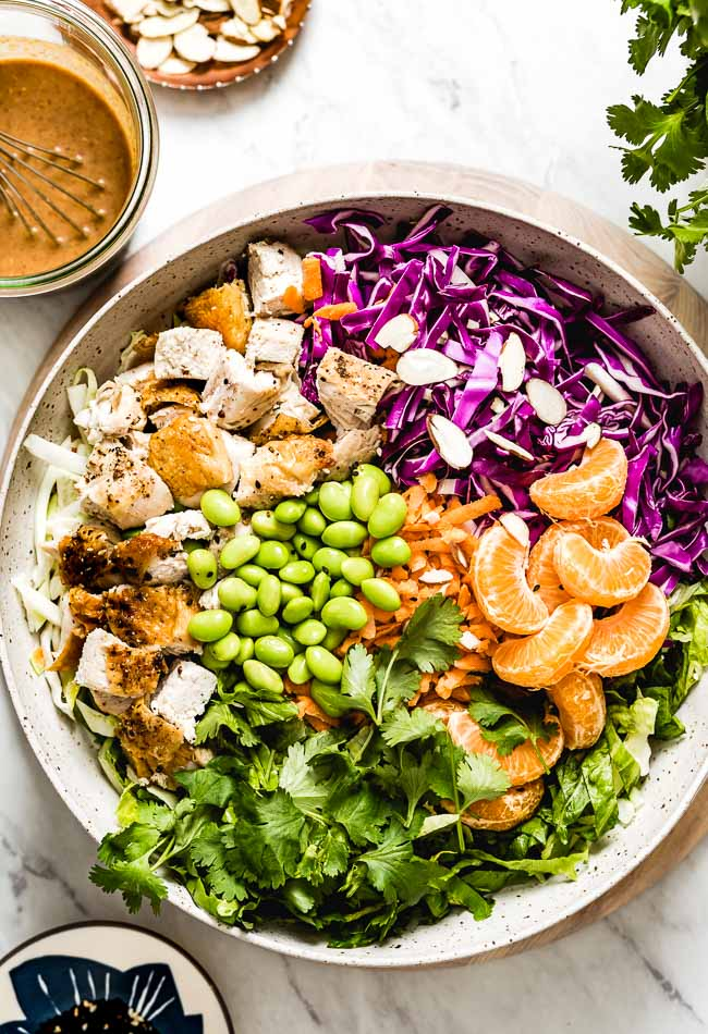 Asian Sesame Chicken Salad recipe in a large bowl with the dressing on the side
