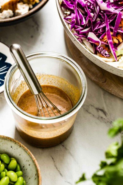 Asian Sesame Ginger Dressing Recipe in a clear jar with a whisk