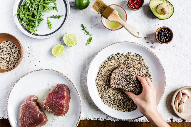 A woman is crusting tuna steaks with sesame seeds