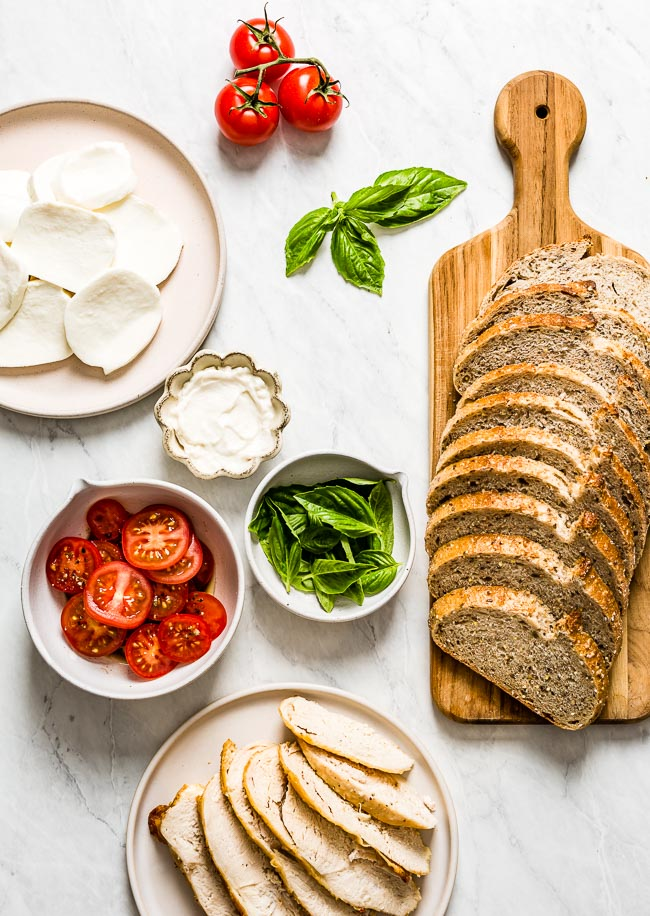 Sandwich ingredients are laid out on a marble backdrop (mozzarella, tomatoes, basil, bread, and chicken)