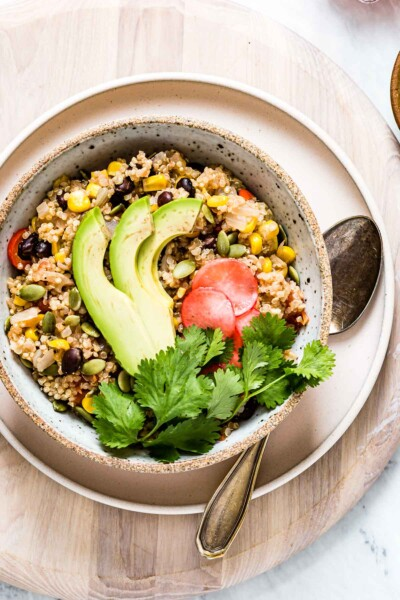 A bowl of Instant Pot Mexican Quinoa garnished with avocados, cilantro, and radishes.