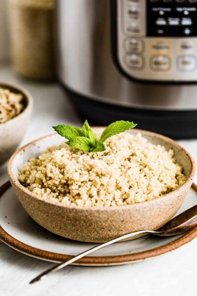 A bowl of cooked quinoa in front of a pressure cooker