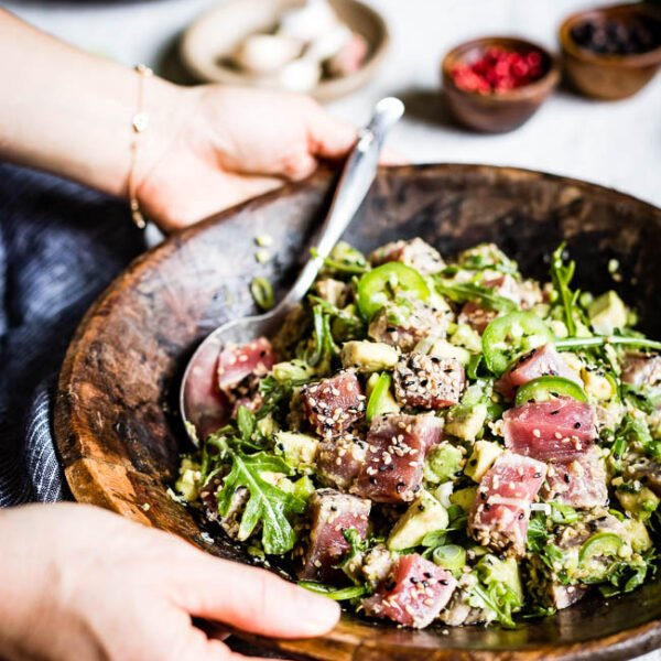 a bowl of pan seared Asian sesame tuna salad is served by a woman