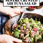 A bowl of ahi tuna salad is being served by a woman