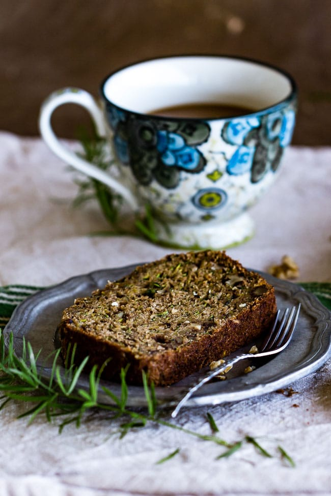 A slice of Zucchini nut bread with a cup of coffee in the background