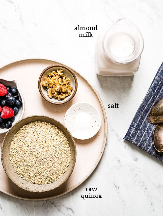 Ingredients for quinoa oatmeal recipe with almond milk with nuts and berries