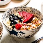 A bowl of Instant pot quinoa breakfast topped off with fruit and granola and served with milk on the side.