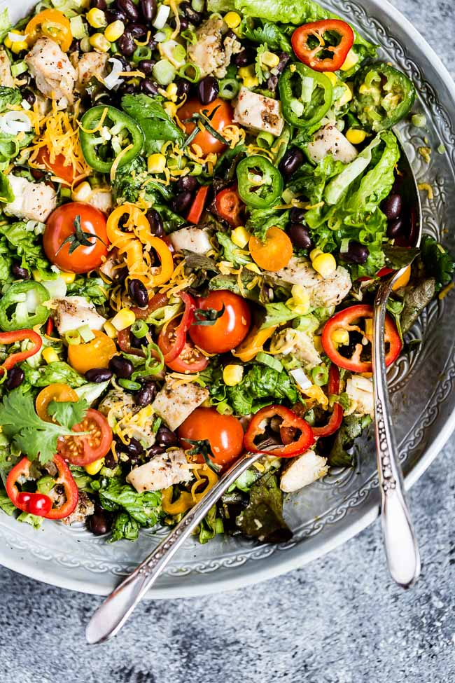 A bowl of southwest chicken salad placed in a salad bowl and photographed from the top
