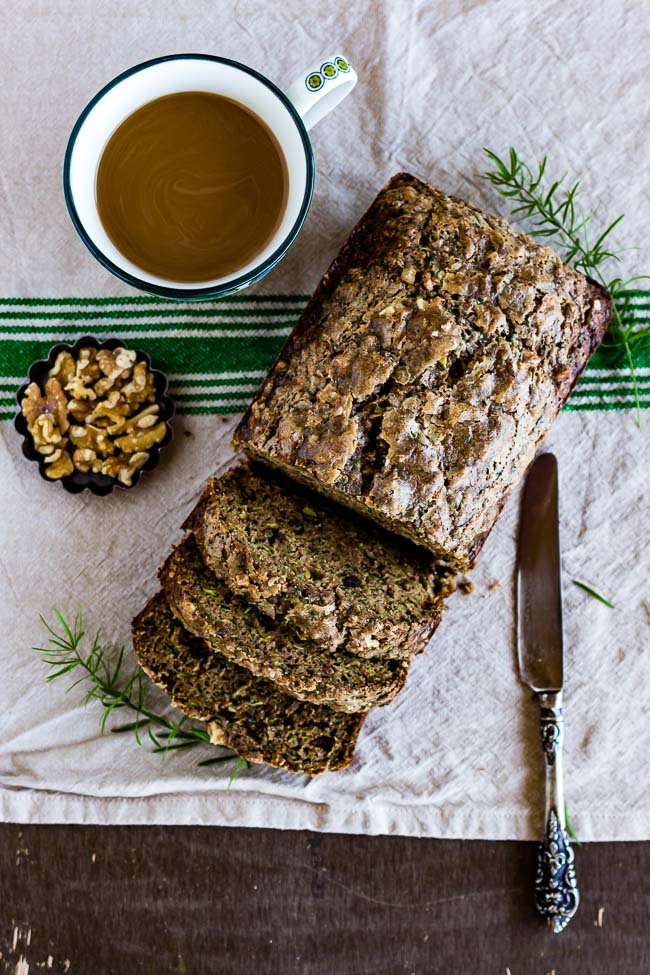 Sliced Zucchini bread with walnuts and a cup of coffee on the side