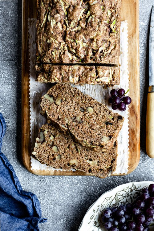 Sliced Vegan Zucchini Bread from the top view with grapes on the side