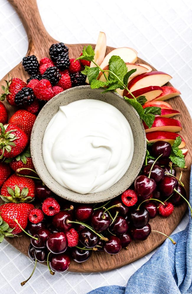 A bowl of yogurt fruit dip surrounded with different kinds of fruit on a wooden cutting board.