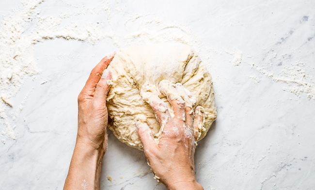 A woman is kneading Challah dough on a marble surface