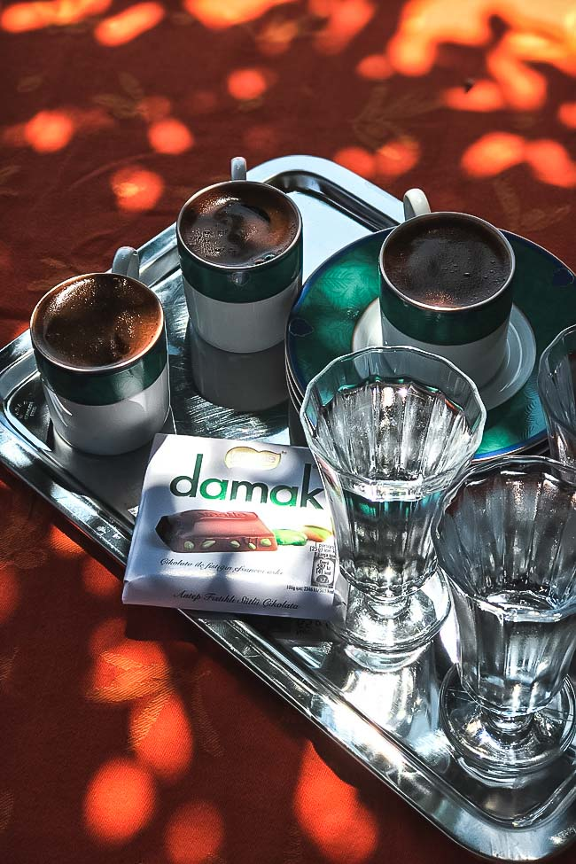 Turkish coffee and chocolate served with water on a silver tray