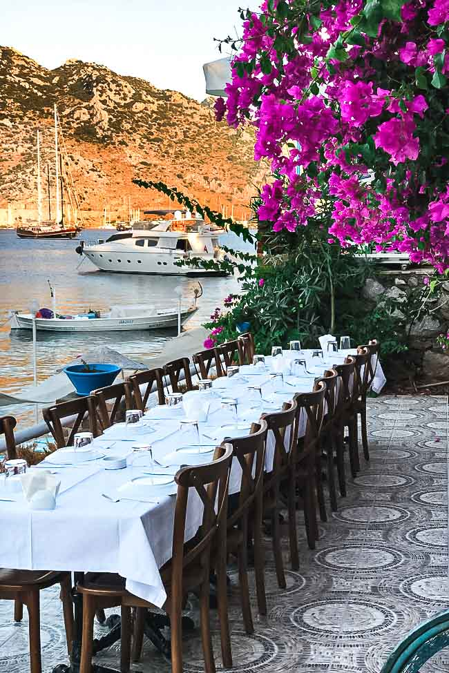 A table set up by the sea with flowers on the side.
