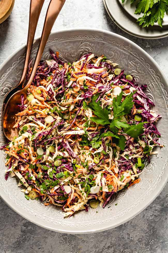 A bowl of healthy coleslaw salad recipe with two spoons in the bowl from the top view