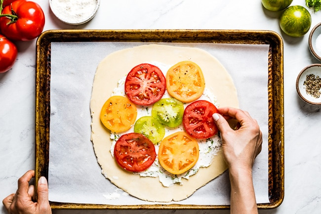 Woman arranging tomatoes on top of the heirloom tomato galette.