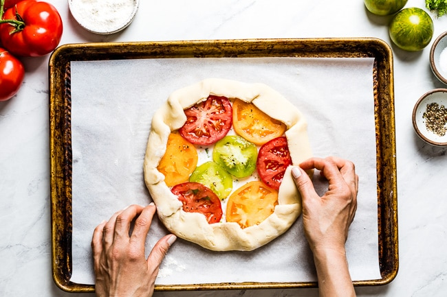 Woman rolling the sides of a tomato galette from the top