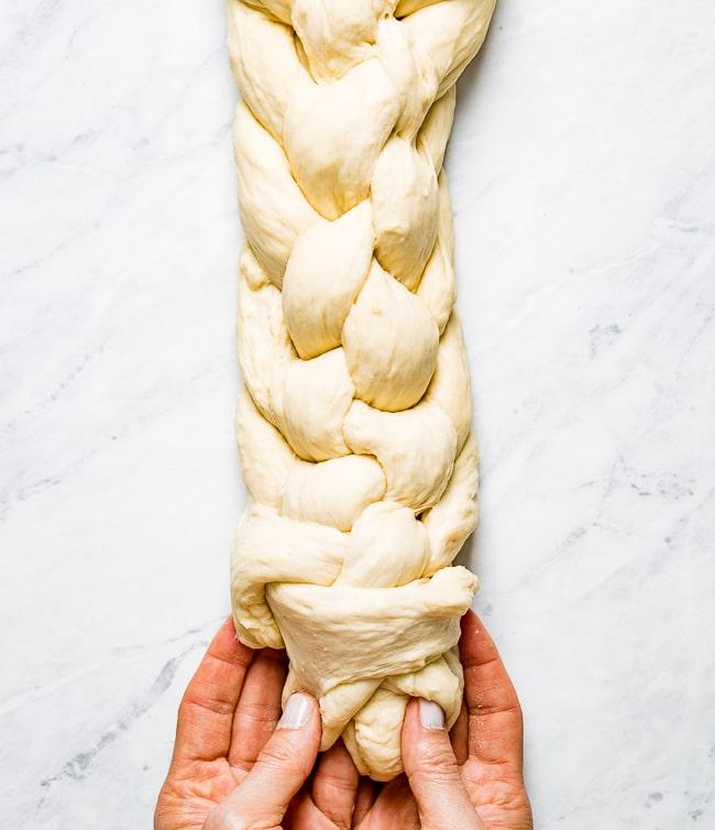 Person braiding Challah bread