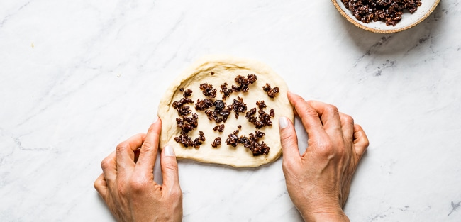 Person filling dough with raisins
