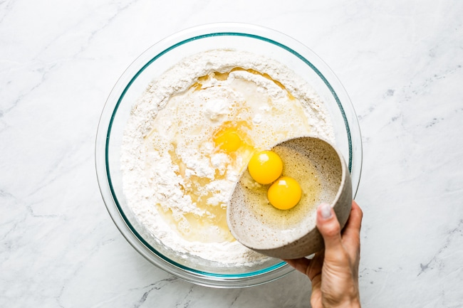 Adding eggs into the bowl with dry ingredients from the top