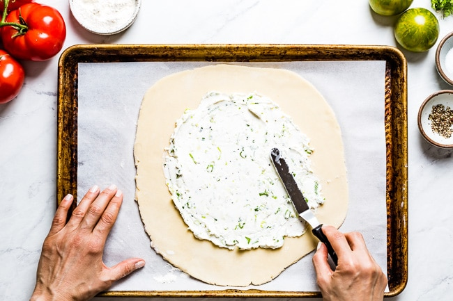 Woman spreading galette dough with goat cheese mixture
