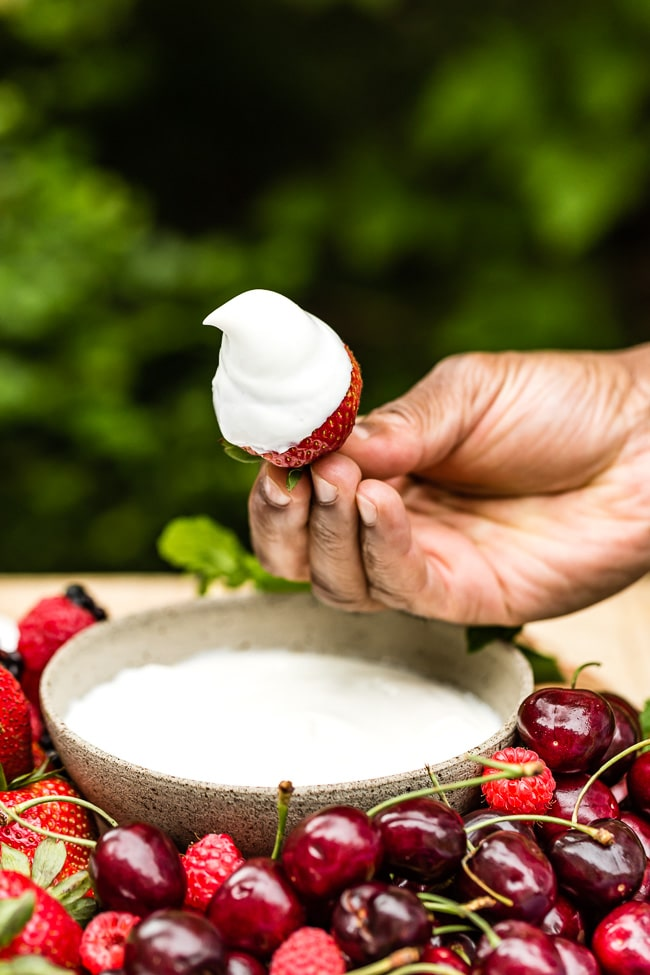 A man is holding a strawberry dipped in yogurt dip.