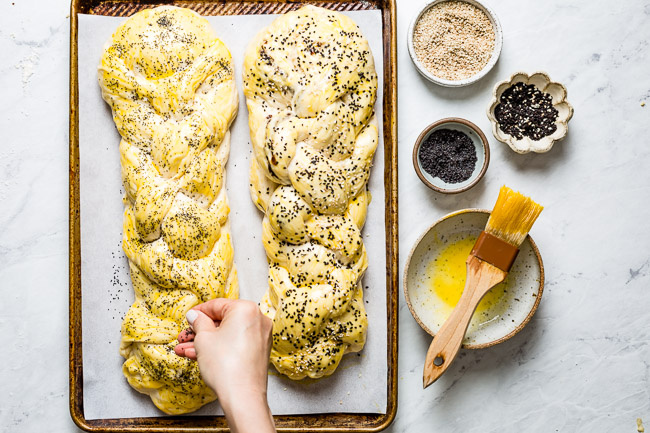 Woman sprinkling homemade Challah bread with poppy seeds